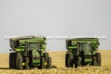 Two John Deere tractors sit in a field at harvest time. John Deere has been lobbying hard against any legislation that gives anyone but dealers the ability to diagnose or fix problems on their tractors.