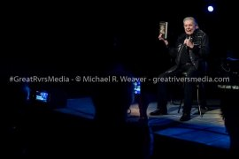 """Mickey Gilley gets a laugh from the crowd as he tells everyone that everyone asks him about what it's like to have Jerry Lee Lewis and Jimmy Swaggart as cousins. As he held up a copy of """"Unconquered"""", he said it's all in here and it's $20."""