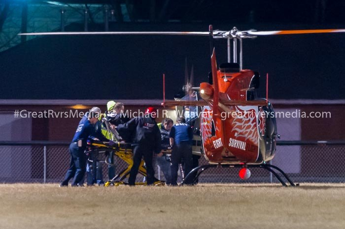 Game official being placed aboard a Survival Flight helicopter at the Calhoun High football field. The time delay between the onset of symptoms to leaving the football field was approximately 52 minutes despite several ambulances on site within minutes.
