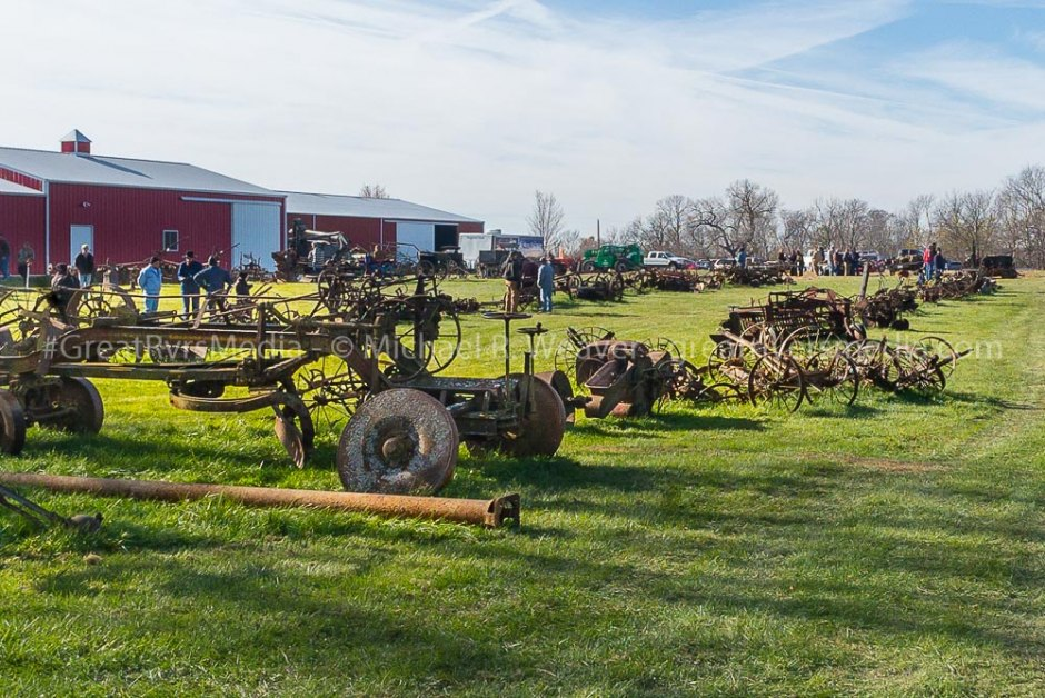 Antique farm equipment in rows waiting to be auctioned.
